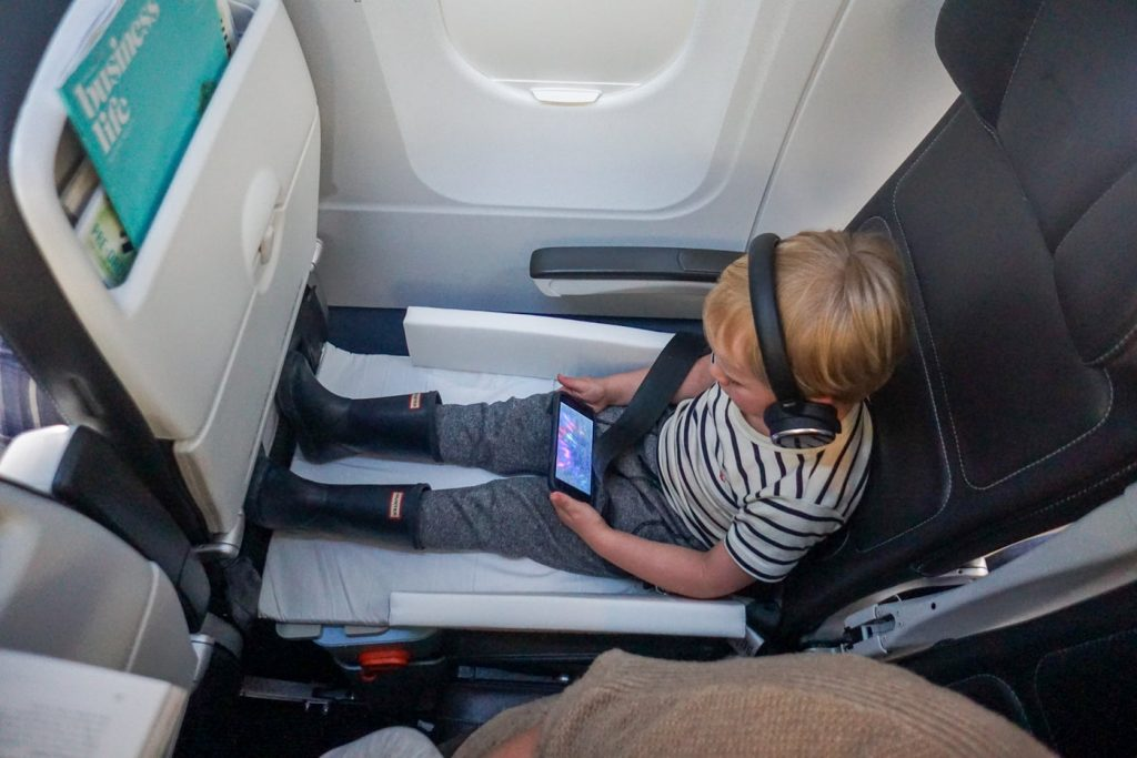 child in seat extender in flight on airplane