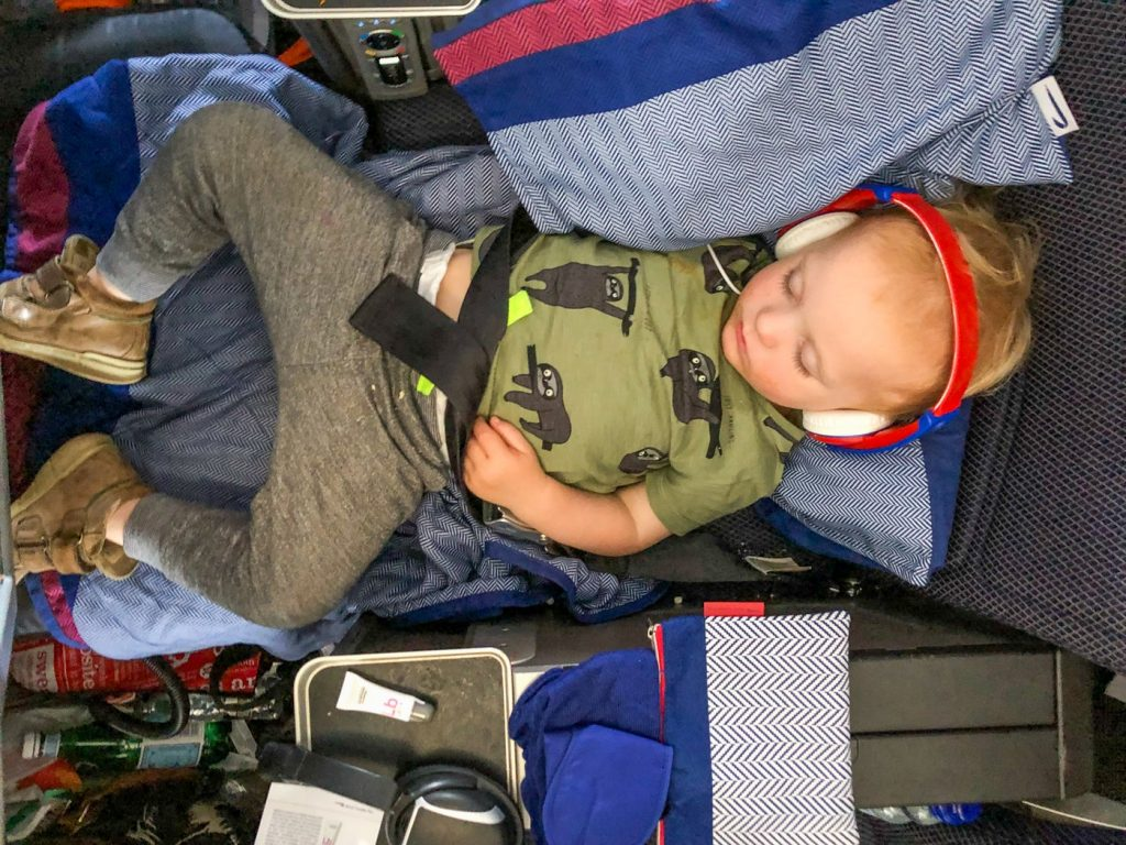 child in seat extender on airplane